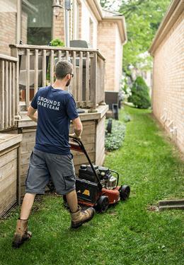 Landscaper mowing lawn